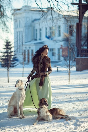 A woman with dark hair with greyhounds on a bright winter day