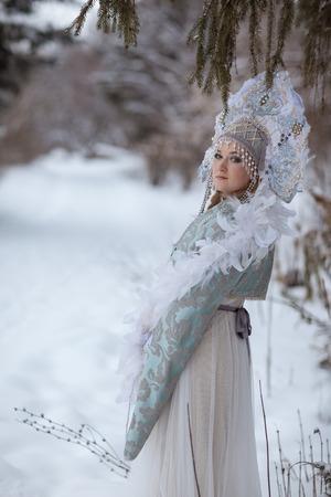 snegurochka: woman in a Snow Maiden costume in a winter forest