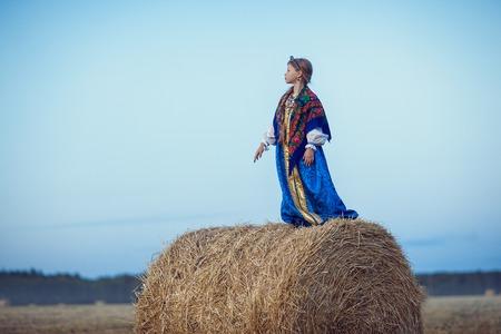 Little girl in Russian costume in the field