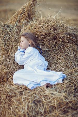 a girl in a shirt in a hayloft