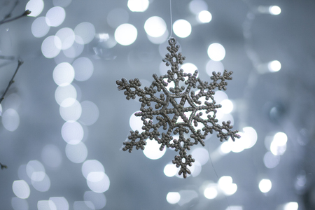 Toy snowflake on a background of lights Stock Photo