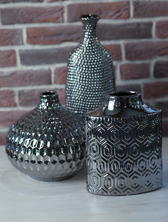 Three Vases Of Stainless Steel On A Brick Wall Background Stock