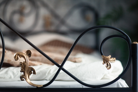Large double wrought iron bed. Bed is covered with white linens