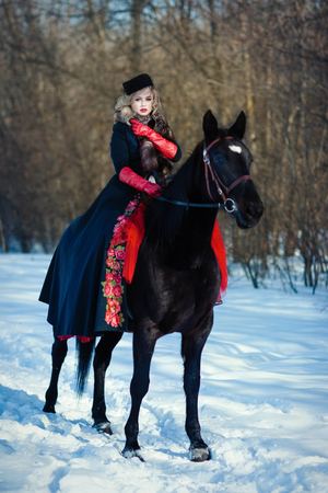 blond woman in red dress with long black coat with dark horse on the background of winter landscape
