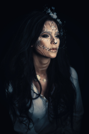 A girl with a stylized make-up of a dead bride. Long-haired brunette in a white shirt Stock Photo