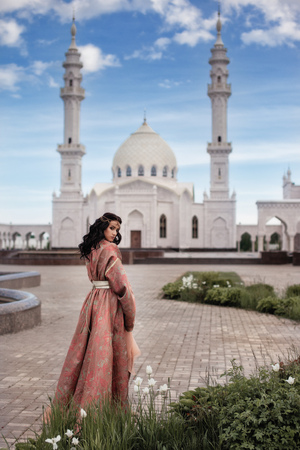 the woman in the red dress against the background of the white mosque