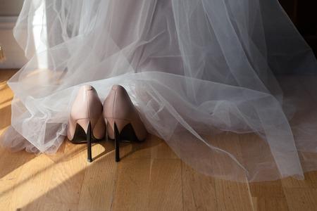 beige shoes of the bride under the wedding dress. Light from the window Standard-Bild - 112880273