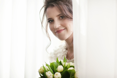 Portrait of a smiling bride with a bouquet of tulips near the window Reklamní fotografie