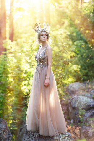Märchenmädchen im Wald. Das Foto wird vom Gegenlicht der Sonne durchdrungen.