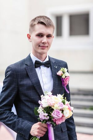 groom with a bouquet of wedding flowers
