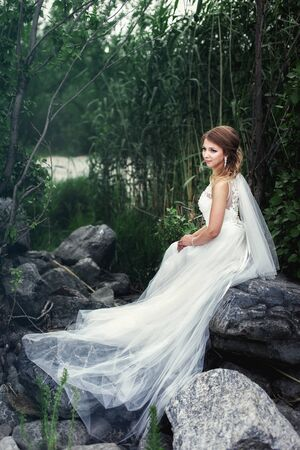 The bride sits on a large stone near the river Standard-Bild