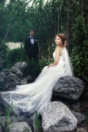 The bride sits on a large stone near the river. A bride stands near the bride