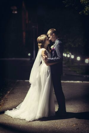 Newlyweds kiss under the lantern at night