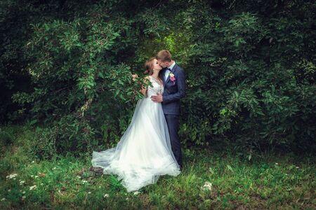 Wedding walk. Happy newlyweds near the green tree Stock Photo