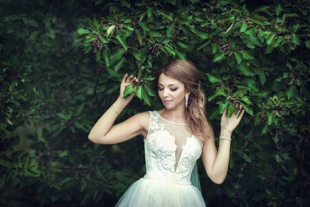 Wedding walk. Bride next to a green tree