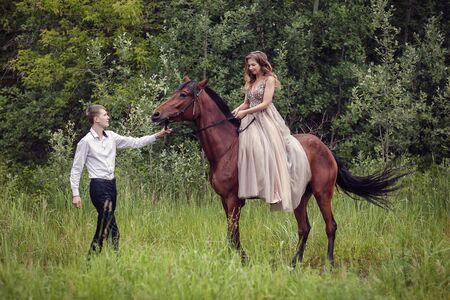 Liebesgeschichte. Zwei Liebende im Wald. Foto mit einem braunen Pferd.