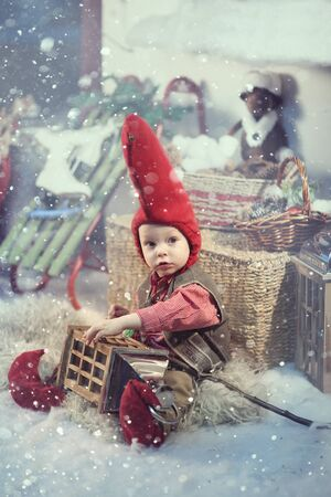 Little christmas gnome in a red cap and vest. Standard-Bild - 138184720