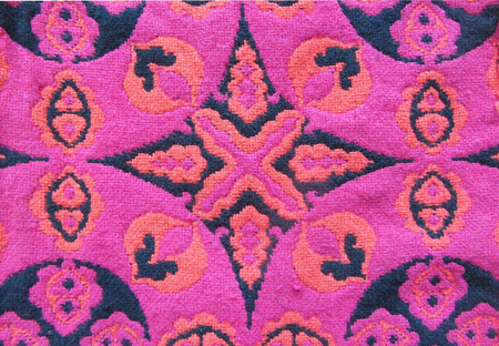 background kaleidoscope: Geometric cotton woven pattern background. Kaleidoscope backdrop. Abstract ornament in black, red, and pink colors.