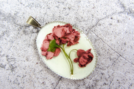 epoxy: Beautiful pendant with flowers in epoxy resin. Womens handmade jewelry, accessory. Stock Photo
