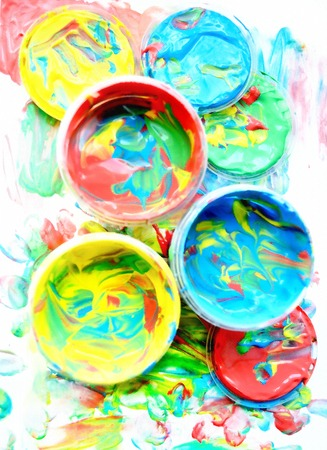 finger paint: Color mixed paint in plastic jars for drawing isolated on white soiled background. Childrens creativity. Finger paint. Paint cans with various colors. Background of Multi Colored Paint. Stock Photo