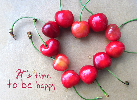 cherishing: Red cherry in shape of heart with stem isolated on grey with text Its time to be happy. Cherry motivational card. Stock Photo