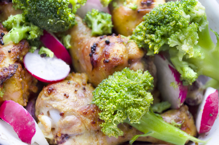 redish: Roasted chicken shin, garnished with spring vegetables: broccoli and redish. Stock Photo
