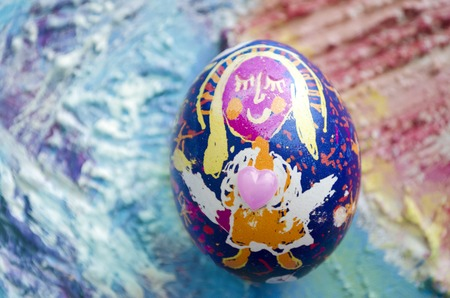 children painting: Single easter egg with beautiful color abstract picture, isolated on colored textured background. Children painting.