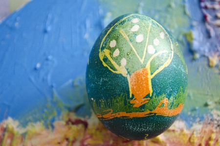 ni�os pintando: Single easter egg with beautiful color abstract picture, isolated on colored textured background. Children painting.