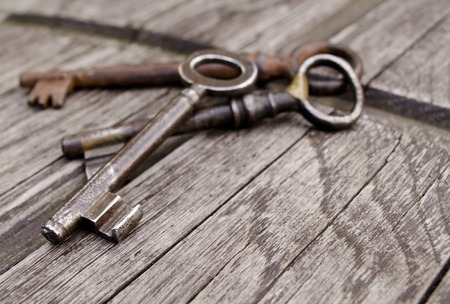 Vintage keys on old wooden background. Close-up. Three old, rustic keys on the table.