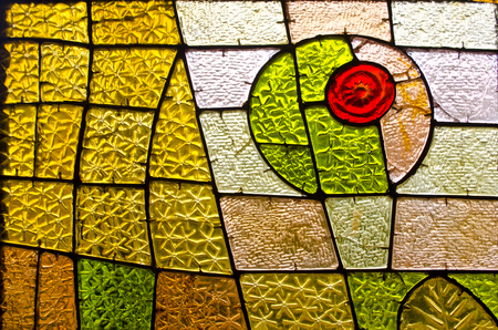 Rectangular and round stained glass window with red rose. Abstract geometric colorful background. Multicolored stained glass church window with irregular random block pattern.