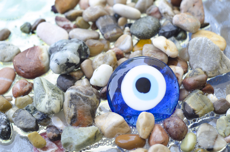 Colorful pebbles on the beach with turkish evil eye glass bead. Background with color stones on the sea and amulet. Sea shore bright stones, pebble, gravel, boulder,