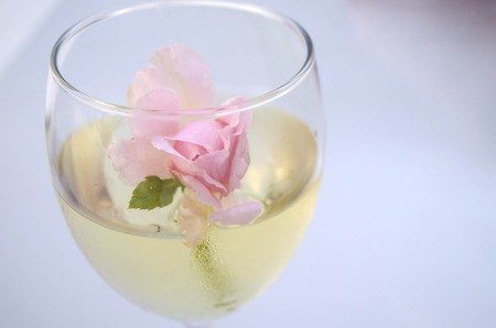 Rose flowers in glass bowl with wine.