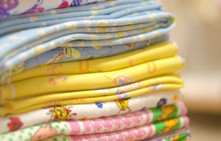 swaddling: Stack of swaddling bands. Close-up of corner a laid colored laundry. Heap of folded linen of various colors. Pile of the washed and ironed linen.