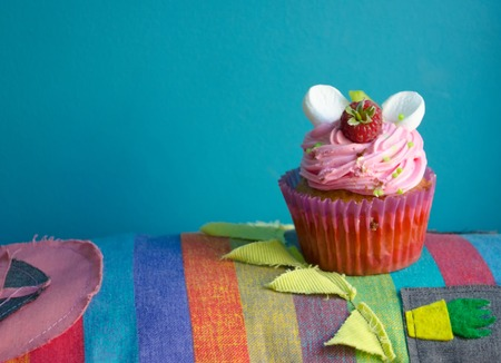 Delicious cupcake on a textile stripped colorful place mat, horizontal with with copy space. Birthday pink cupcake with raspberries. Stock Photo
