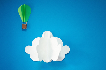 isolates: Handmade hot air balloon and cloud in the sky. Paper art style. Isolates on blue background. Blank for motivating quote, note, message and comment. Idea for poster, banner, flyer.