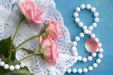 Bouquet of roses and pearl necklace in a figure 8. Womens Day greeting card. 8 March. International Happy Womens Day. The 8th of March banner and poster.