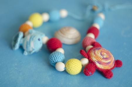 Halskette aus gestrickten Perlen und Spielzeug für das Baby in einer Schlinge sitzen. Gestrickte Perlen. Sling Halskette. Standard-Bild - 78129514