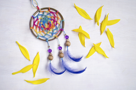 Dreamcatcher With Blue Feathers Between The Yellow Sunflower Petalson An Wooden Background Ethnic Design