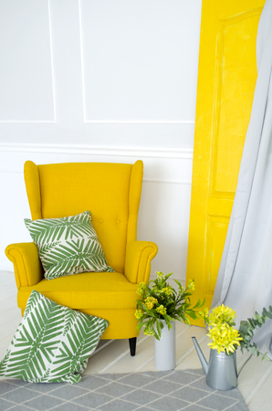 Yellow armchair in the interior with elements of home textiles, pillows and floral decor.
