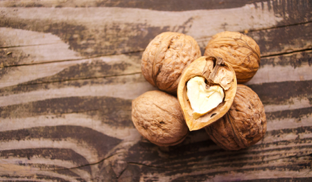 Walnuts on a textured wooden table. Assortment of nuts isolated on rustic old wooden background and splintered walnut with heart-shaped core. Walnuts close up.