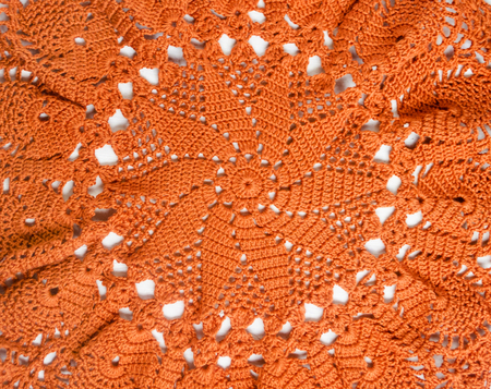 Orange crocheted handmade handkerchief in the form of sunflower.