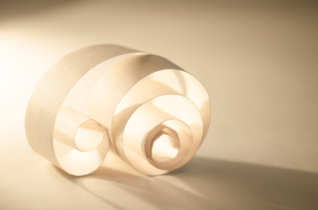 Abstract curl of paper. Light and shadow on a golden background. Paper waste. Stock Photo
