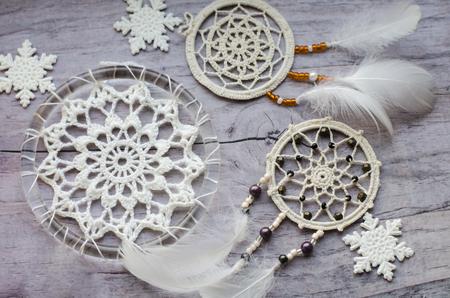 Dreamcatcher mit Federn auf einem hölzernen Hintergrund. Ethnisches Design, Boho-Art, Stammes- Symbol. Weiße Weihnachts- und Neujahrsschneeflocke auf einem alten Hintergrund der hölzernen Weinlese.