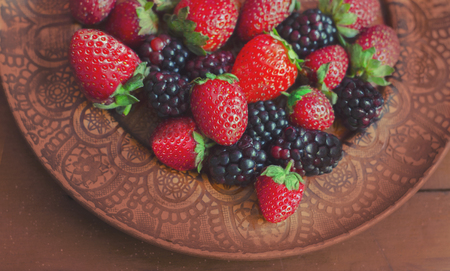 Blackberries and strawberries on a clay plate with an ornament on a wooden background. Photos of useful super food.