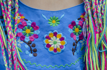 Mexican embroidery with colored thread on a blue background. Cotton thread satchels.