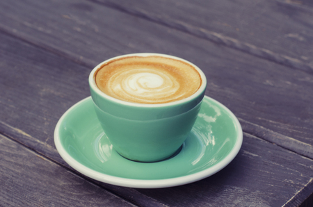 Turquoise cup with latte on a wooden background. Still life in vintage style