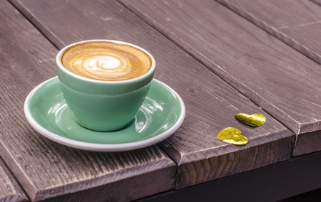 Turquoise Latte Cup on a wooden background with golden hearts. Still Life to Valentine's Day.