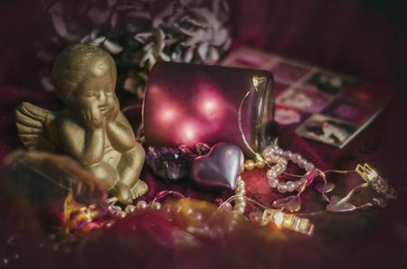 Composition with a golden cupid, gift box, heart, hydrangea flower in mystical dark lighting. Valentine's Day