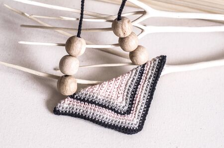 Handcrafted accessories in Scandinavian style. Tie in the form of a triangle, knitted of wooden beads. Original accessory in ethnic style.