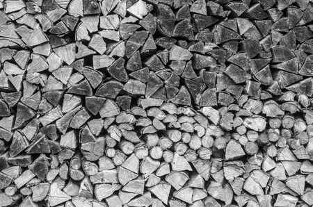 Background of splitted, dried and stacked firewood. Bunch of wood. Black and white photo. 版權商用圖片